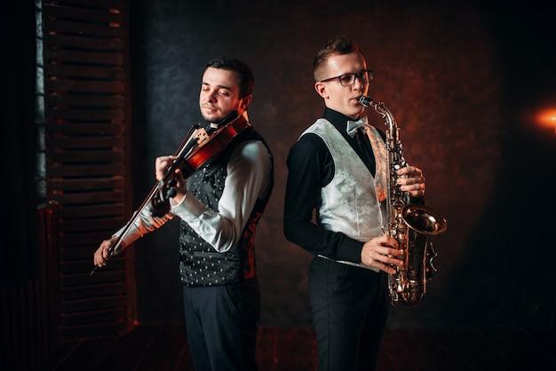 Саксофонист и скрипка играют классическую мелодию Premium Фотографии