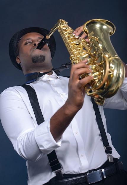 Saxophonist black man playing the saxophone. Premium Photo