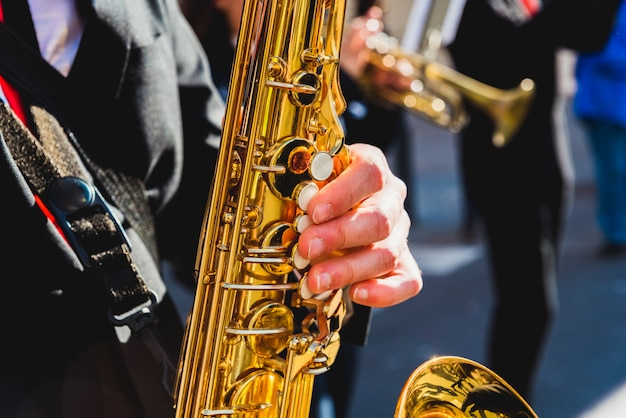 Saxophonist fingers playing a piece during a street festival. Premium Photo
