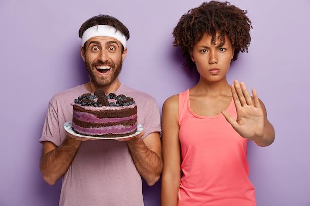Dì no al mangiare dannoso! la donna dalla pelle scura seria mostra il gesto di arresto Foto Gratuite