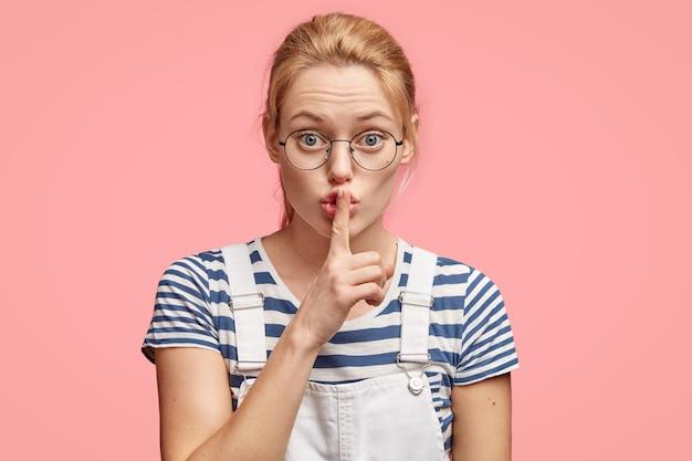 これ以上言わない!美しい真面目なヨーロッパの女性は、静かなジェスチャーをし、唇に前指を保ち、静かにするように頼みます 無料写真