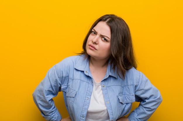 非常に怒っている誰かをscる若い曲線美プラスサイズの女性。 Premium写真