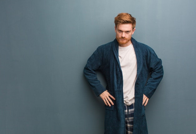 非常に怒っている誰かをscるパジャマで若い赤毛の男 Premium写真