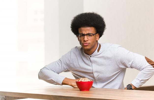 非常に怒っている誰かをscる朝食を持っている若い黒人男性 Premium写真