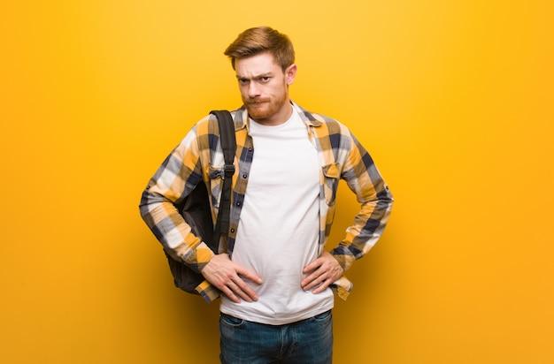 非常に怒っている誰かにscる若い赤毛学生男 Premium写真