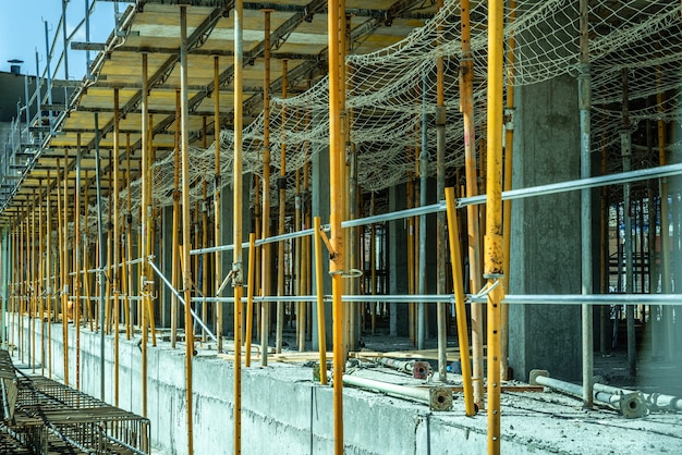 Scaffolding holding the concrete pillars formwork of some buildings under construction. Premium Photo