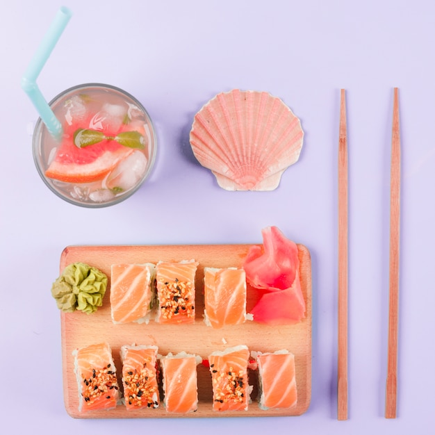 Scallop seashell; grapefruit juice; chopsticks; salmon sushi served with wasabi and pickled ginger on chopping board against purple backdrop Free Photo