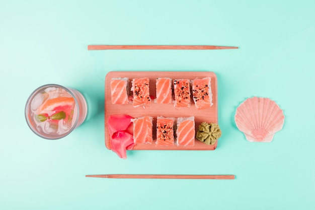 Scallop seashell and grapefruit juice with salmon sushi served with wasabi and pickled ginger on chopping board against mint backdrop Free Photo