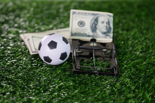 Scam with soccer or football gambling corruption like a ball with mousetrap Premium Photo