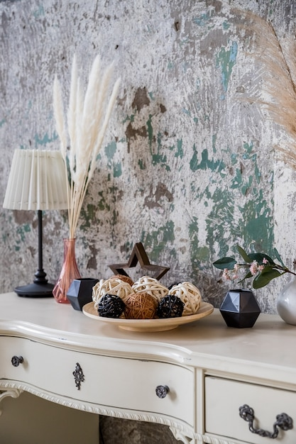 Scandinavian decoration for cozy home made with dry herbs, lamp, candles and garlands on concrete wall.elegant personal accessories and plants. home decor.eco-style Premium Photo