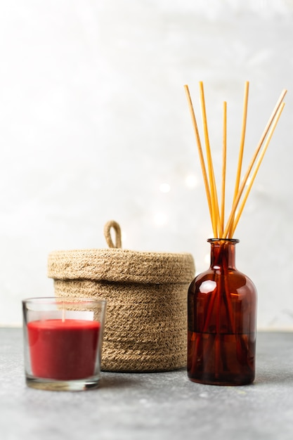Scandinavian hygge style, home interior  scent aroma diffuser with wooden sticks, small straw basket, red candle, Premium Photo