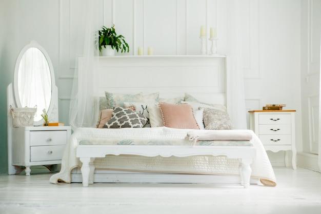 Белая спальня в скандинавском стиле. четыре подушки на кровати. современный интерьер Premium Фотографии