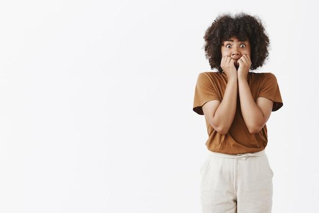 Напуганная афроамериканская девочка-подросток в ступоре выскакивает глаза и прикрывает рот, чтобы не кричать руками в ужасе и испуге дрожит от страха и шока Бесплатные Фотографии
