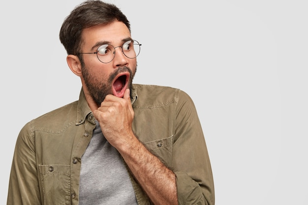 Scared anxious male keeps hand near opened mouth, looks with very frightened expression aside, notices something awful, wears round spectacles and fashionable shirt, poses in against white wall Free Photo