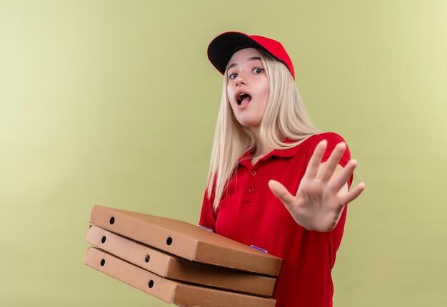 孤立した緑の背景に停止ジェスチャーを示すピザボックスを保持しているキャップで赤いtシャツを着て怖い配達の若い女の子 無料写真