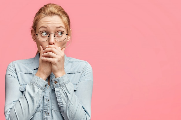 Scared female tries to be silent, keeps hands on mouth, looks with worried expression away, dressed in casual denim jacket, isolated over pink Free Photo