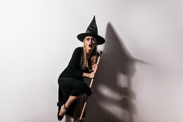 Испуганный женский волшебник, держащий волшебную метлу. крытая фотография испуганной женщины в костюме ведьмы, позирующей в хэллоуин. Бесплатные Фотографии