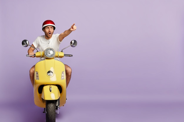 Scared guy with helmet driving yellow scooter Free Photo