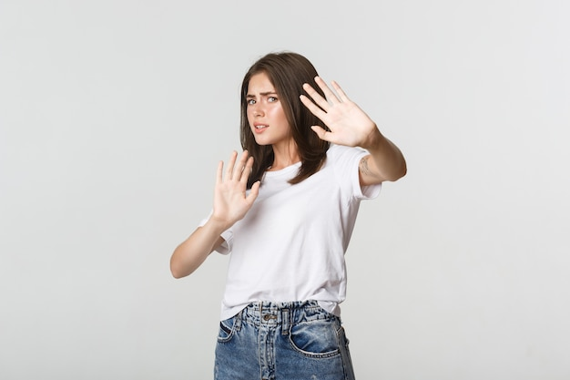 Scared and insecure cute girl raising hands in stop gesture, defending herself. Free Photo