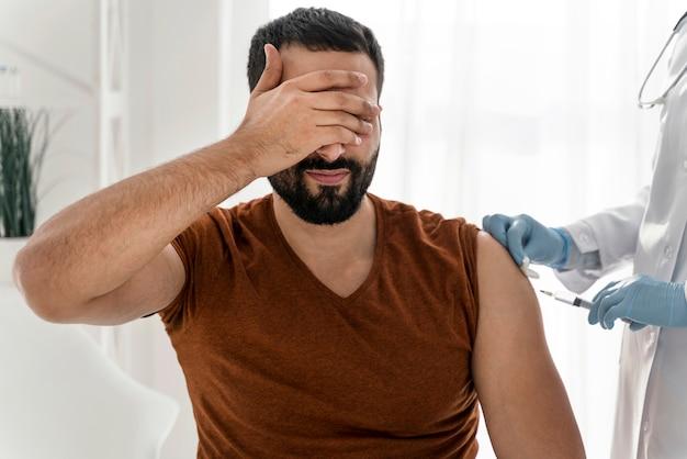 予防接種を受ける前に目を覆っている怖い男 無料写真