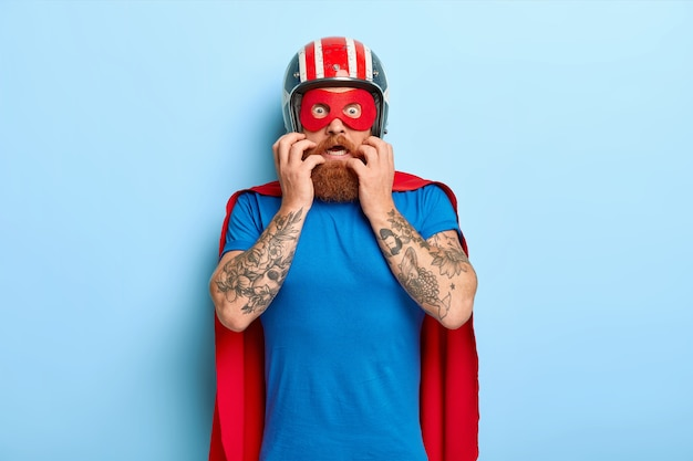 무서워하는 긴장된 남자는 두려움으로 보이고 헬멧, 빨간 마스크 및 망토를 착용하고 비행을 준비합니다. 무료 사진