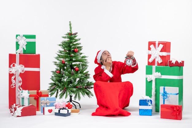Babbo natale spaventato in pensieri profondi seduto per terra e mostrando orologio vicino a doni e albero di natale decorato su sfondo bianco Foto Gratuite