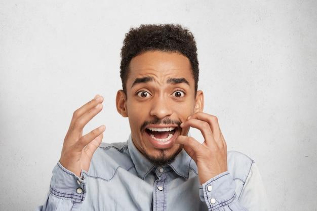 Испуганный, шокированный темнокожий мужчина тревожно жестикулирует, смотрит с широко открытым ртом и глазами, Бесплатные Фотографии
