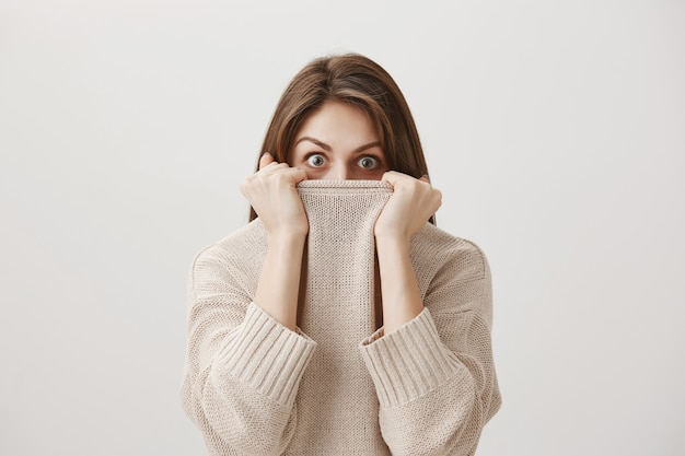 Scared timid girl hiding face in sweater collar and alarmed Free Photo