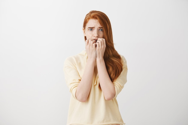 Scared timid redhead girl looking frightened Free Photo