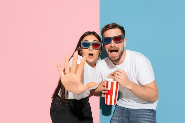 ポップコーンで3dシネマを見るのが怖い。ピンク、ブルーの二色の壁にカジュアルな服を着た若くて幸せな男性と女性。人間の感情、表情、関係の概念。美しいカップル。 無料写真