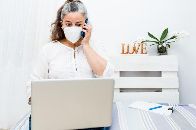 Страшно женщина сидит на диване дома с помощью ноутбука и звонит по телефону с антивирусной маской Premium Фотографии