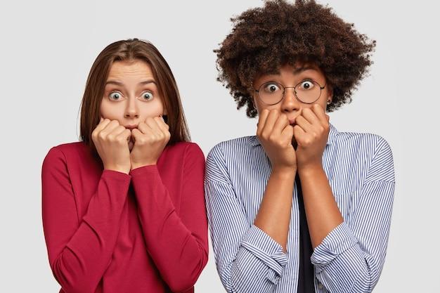 怖がっている女性は心配そうに見え、指の爪を噛み、虫の目で見つめます 無料写真