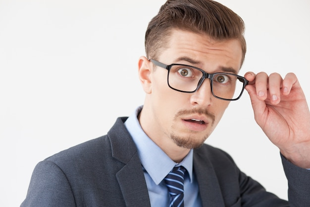 Scared Young Business Man Adjusting Glasses Free Photo