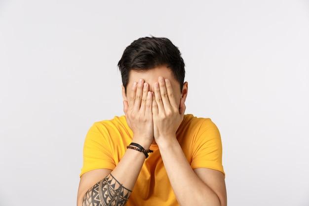 Испуганный молодой парень закрывает лицо ладонями, так как не хочет смотреть ужасную сцену в фильме, стоит белая стена в страхе, выражает испуг и неуверенность, прячет глаза, стоит белая стена с завязанными глазами Premium Фотографии