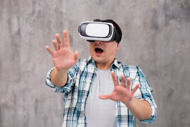 Scared young man with raised hands in vr headset Free Photo