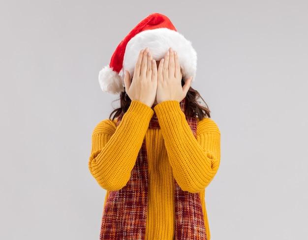 サンタの帽子と手で顔を閉じる首の周りにスカーフを持つ怖い若いスラブの女の子 無料写真