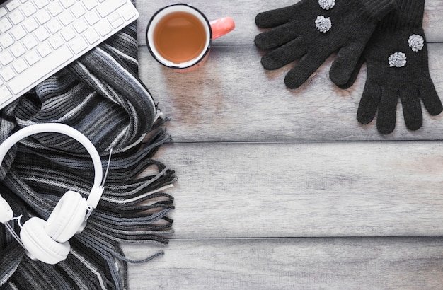 Scarf and gloves near tea and devices Free Photo