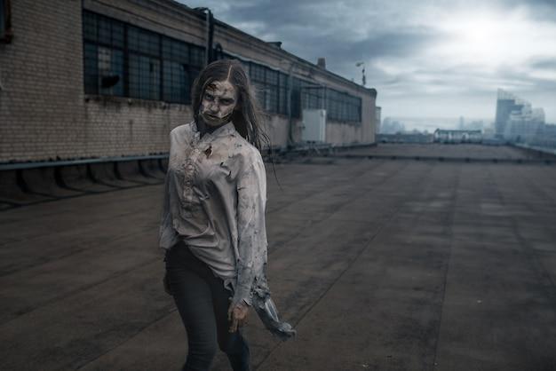 廃墟の屋上にいる怖い女性ゾンビ、致命的な追跡。都市の恐怖、不気味な這いつくばりの攻撃、黙示録 Premium写真