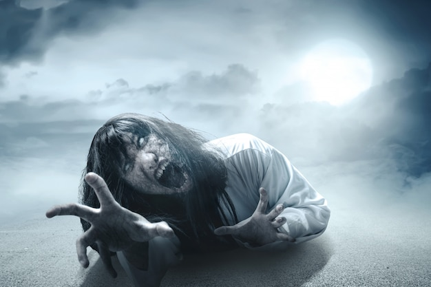 Scary ghost woman with blood and angry face with clawing hands crawling in the dark Premium Photo