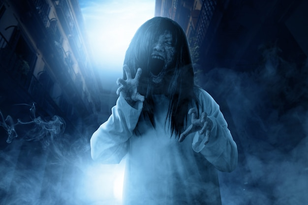 Scary ghost woman with blood and angry face with clawing hands haunted the abandoned building Premium Photo