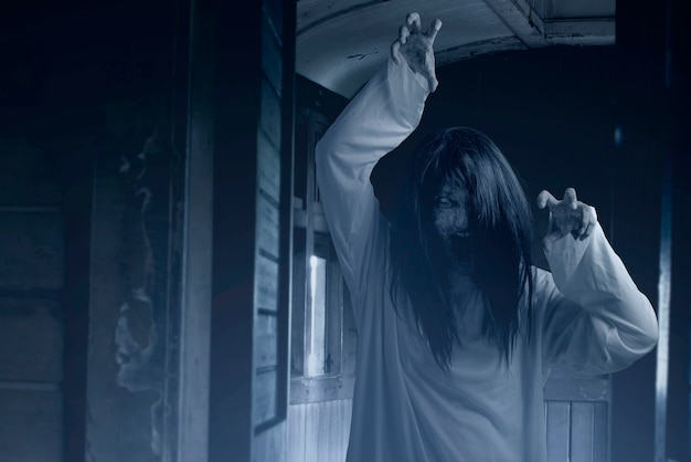 Scary ghost woman with blood and angry face with clawing hands on the old wagon Premium Photo