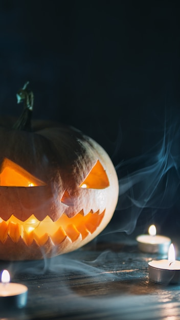 Premium Photo Scary Pumpkin Lantern With Creepy Face On Dark Background With Clouds Of Steam