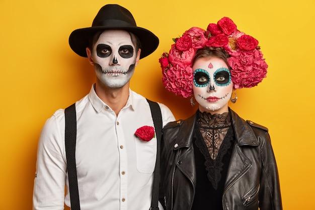 무서운 여자, 남자는 창조적 인 해골 메이크업, 가죽 검은 색 재킷, 모자, 모란 화환을 착용하고 할로윈 카니발이나 의상 파티 준비 무료 사진