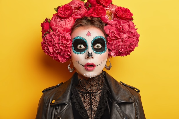 怖い女性はホラーハロウィーンの化粧をして、恐怖の表情をしていて、目の周りに暗い塗られた円を追いかけ、黄色の背景の上に隔離された大きな赤い花の花輪を着ています。 無料写真
