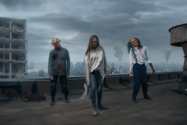 廃墟の屋上にいる恐ろしいゾンビ軍、致命的な追跡。都市の恐怖、不気味な這いつくばりの攻撃、黙示録 Premium写真