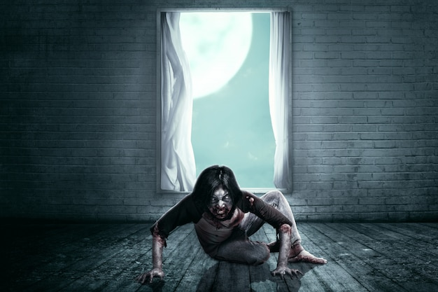 Scary zombies with blood and wound on his body crawling on the abandoned house Premium Photo