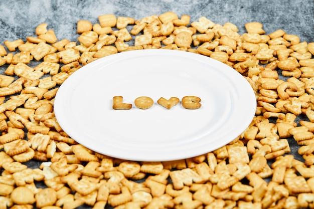 Разбросанные крекеры алфавита и слова любви написанные крекерами на белой тарелке. Бесплатные Фотографии