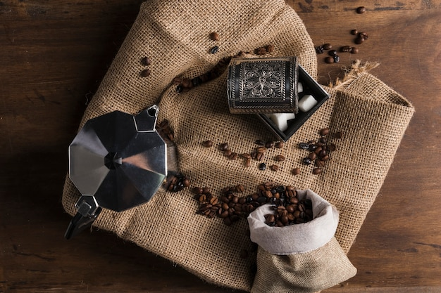 Fagioli sparsi dal sacco vicino a caffettiera e scatola di zucchero Foto Gratuite