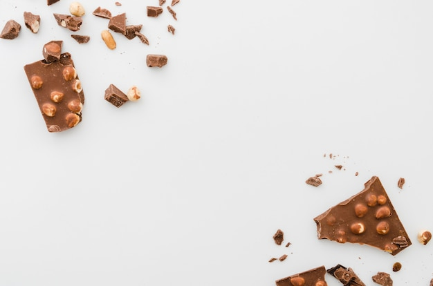 Scattered broken nut chocolate on white background Free Photo