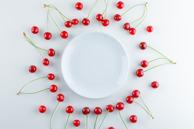 Scattered cherries with empty plate, flat lay. Free Photo